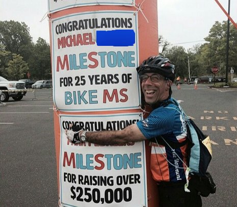 Bike Mike hugs 25th year banner for him in 2015